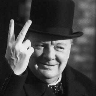 Photo de Winston Churchill faisant le signe de la victoire, paume tourner vers lui.